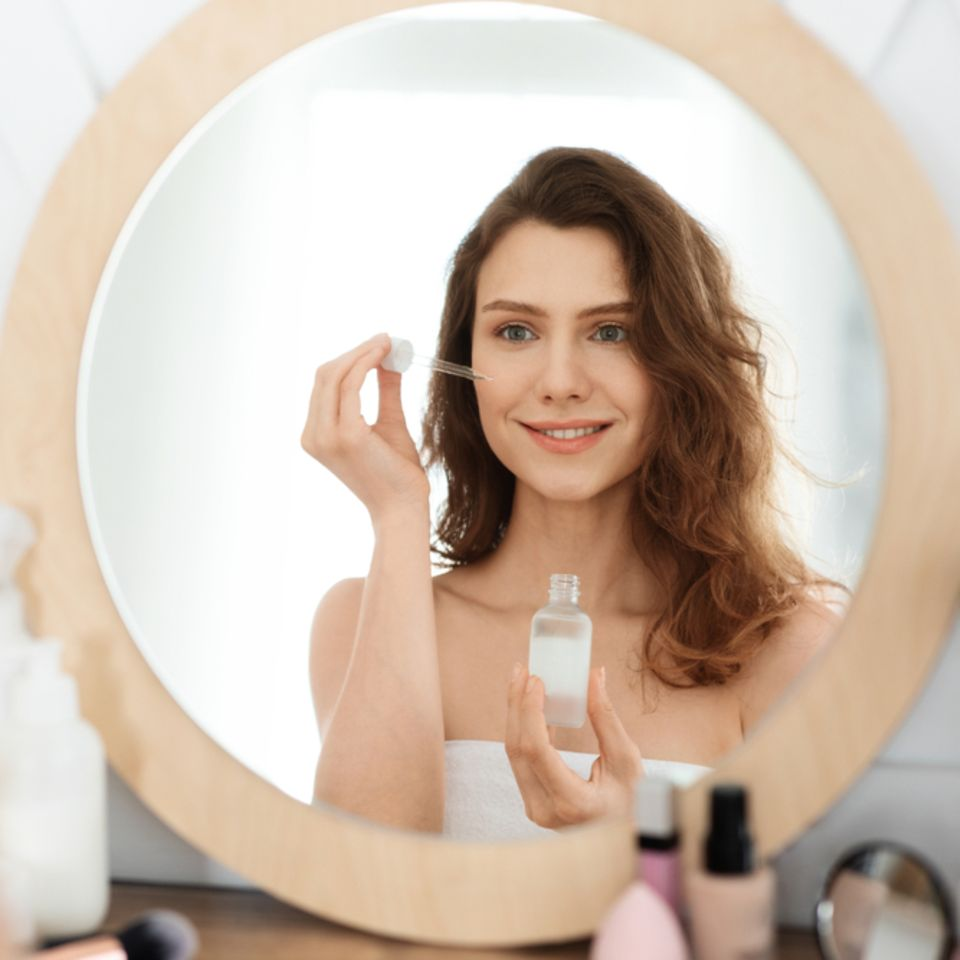 Schöne Frau benutzt Serum vor Spiegel