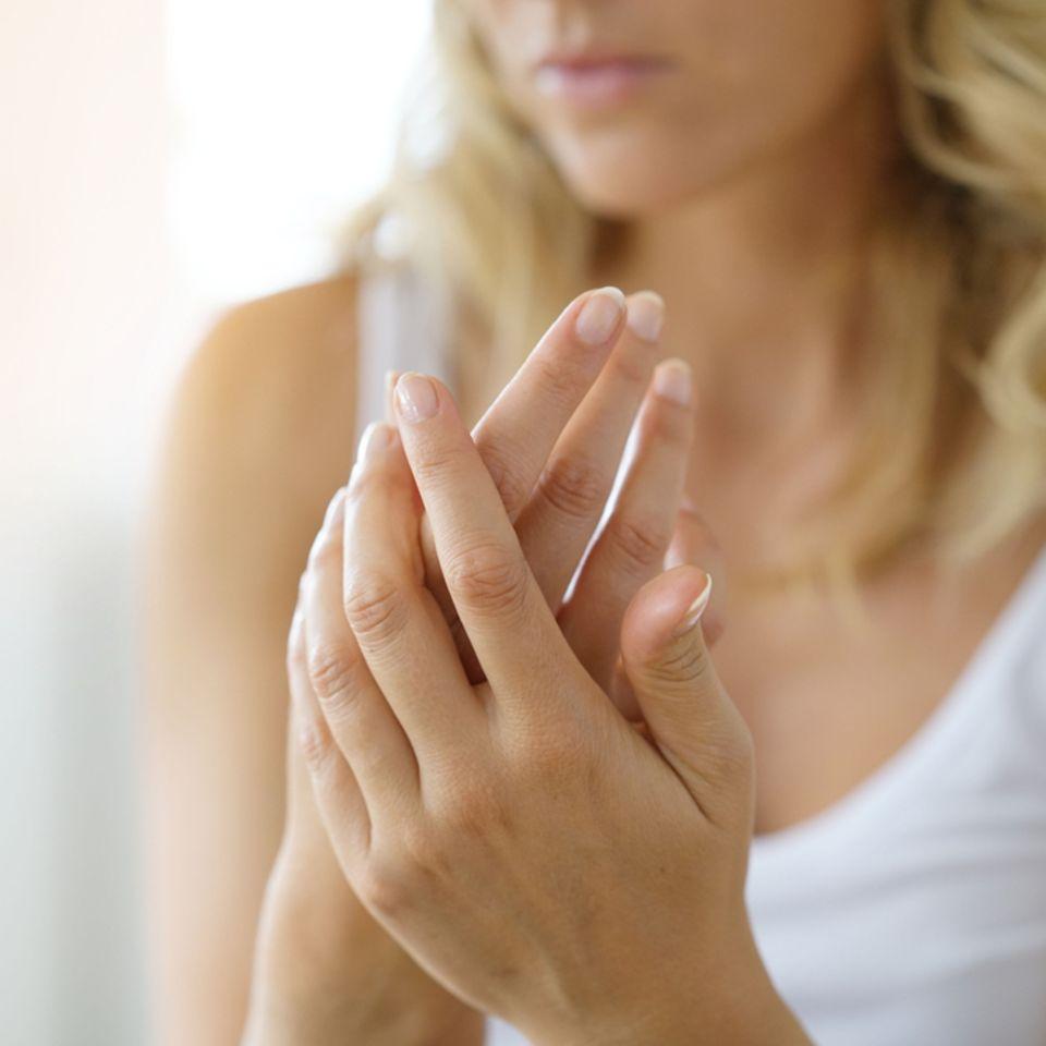 Hände einer Frau beim Verwenden von Handcreme