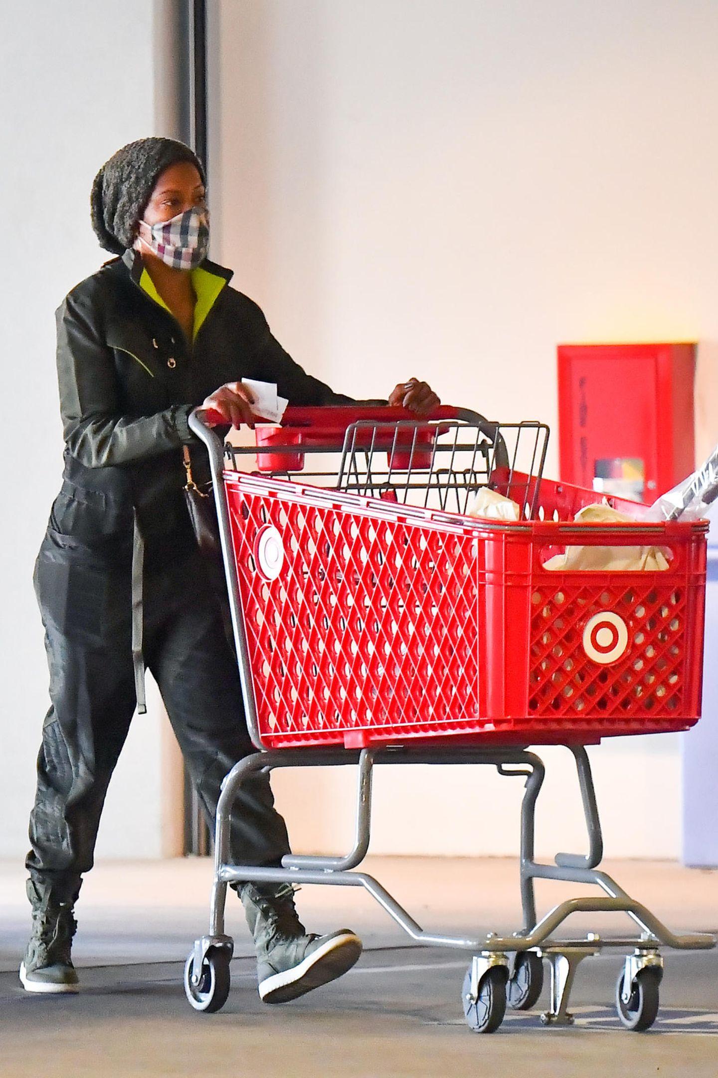 Mit einem abgestempelten Parkticket in der einen und einem gefüllten Einkaufswagen in der anderen Hand verlässt Regina King eine Target-Filiale in Los Angeles. Ihren Einkauf erledigt sie in bequemen Sneakern, die perfekt zu ihrem olivfarbenen Overall und der Beanie passen.