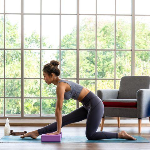 Frau bei einer Yogapose, Yoga, Yoga-Block, Frau in Sportkleidung