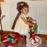 Kleine Zöpfchen, niedliches Kleid: Wer fährt hier ganz stolz Dreirad mit Puppe auf den Gepäckträger?