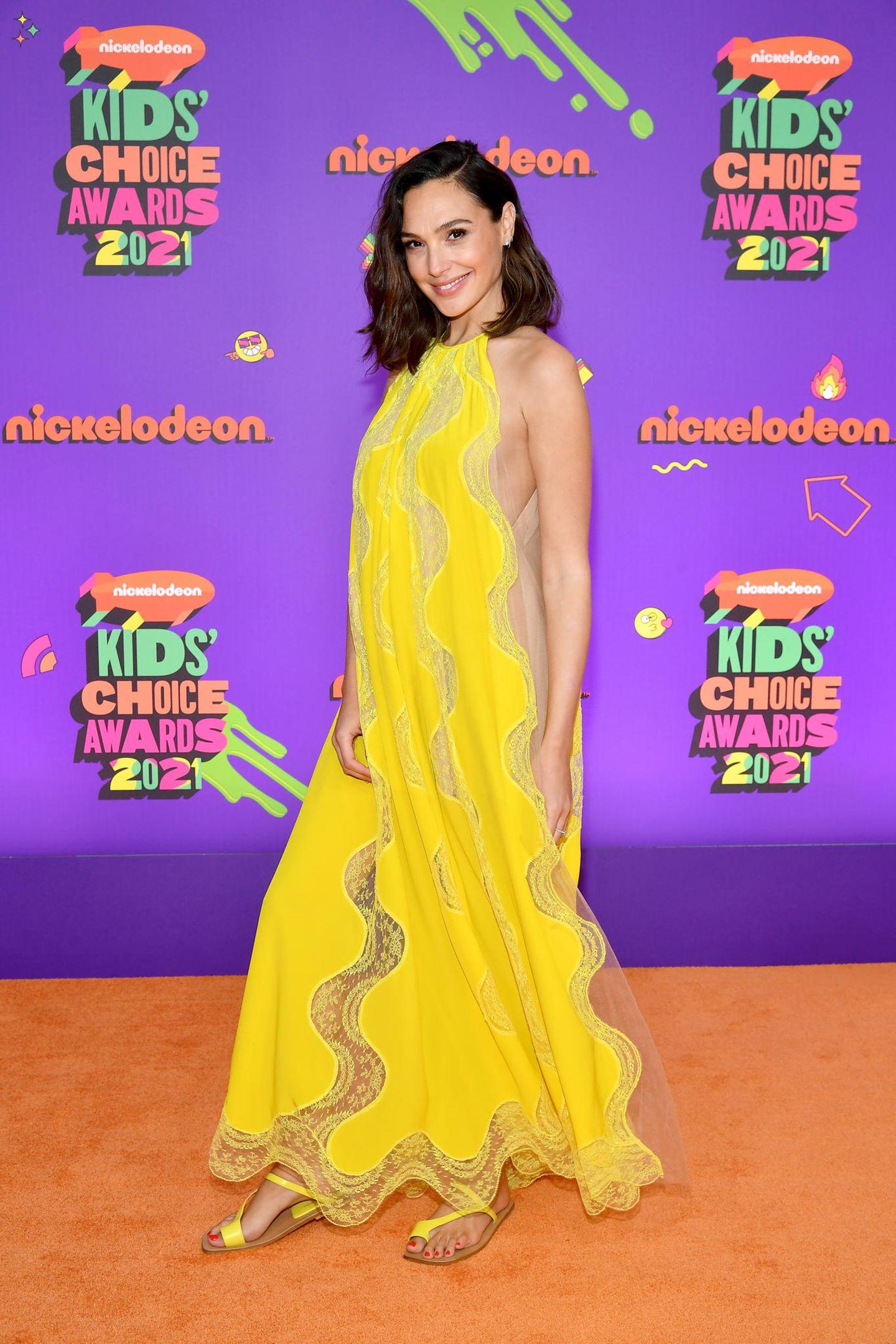 """Vor wenigen Tagen erst verkündetGalGadot, dass sie zum dritten Mal Mama wird, jetzt gibtes auch schon die erste Gelegenheit, die Babykugel auszuführen – bei den Kids Choice Awards 2021. In einer sonnengelben Robe läuft der """"Wonderwoman""""-Star über den orangefarbenen Teppich der Preisverleihung und auch wenn das voluminöse Kleid die Babykugel die meiste Zeit gut versteckt, so ist die kleine Wölbung doch nicht mehr zu übersehen."""