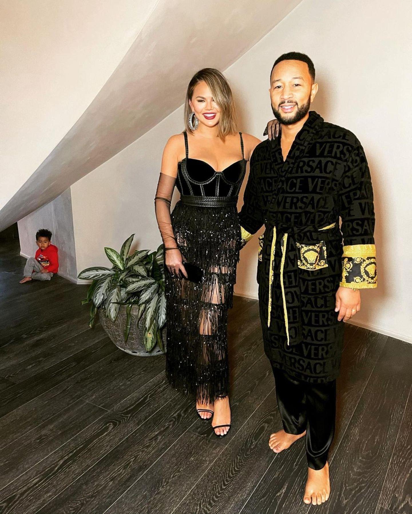 Die Grammys wurden in diesem Jahr zuhause gefeiert – aber Chrissy Teigen und John Legend haben sich trotzdem in Schale geworfen und begeistern im Versace-Look. Ob Söhnchen Miles (ganz links versteckt) auch so angetan ist?