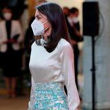 In Kragen und Bündchen der cremefarbenen Bluse wird das Muster wieder aufgegriffen. Dazu trägt Königin Letizia eine beigefarbene Clutch.