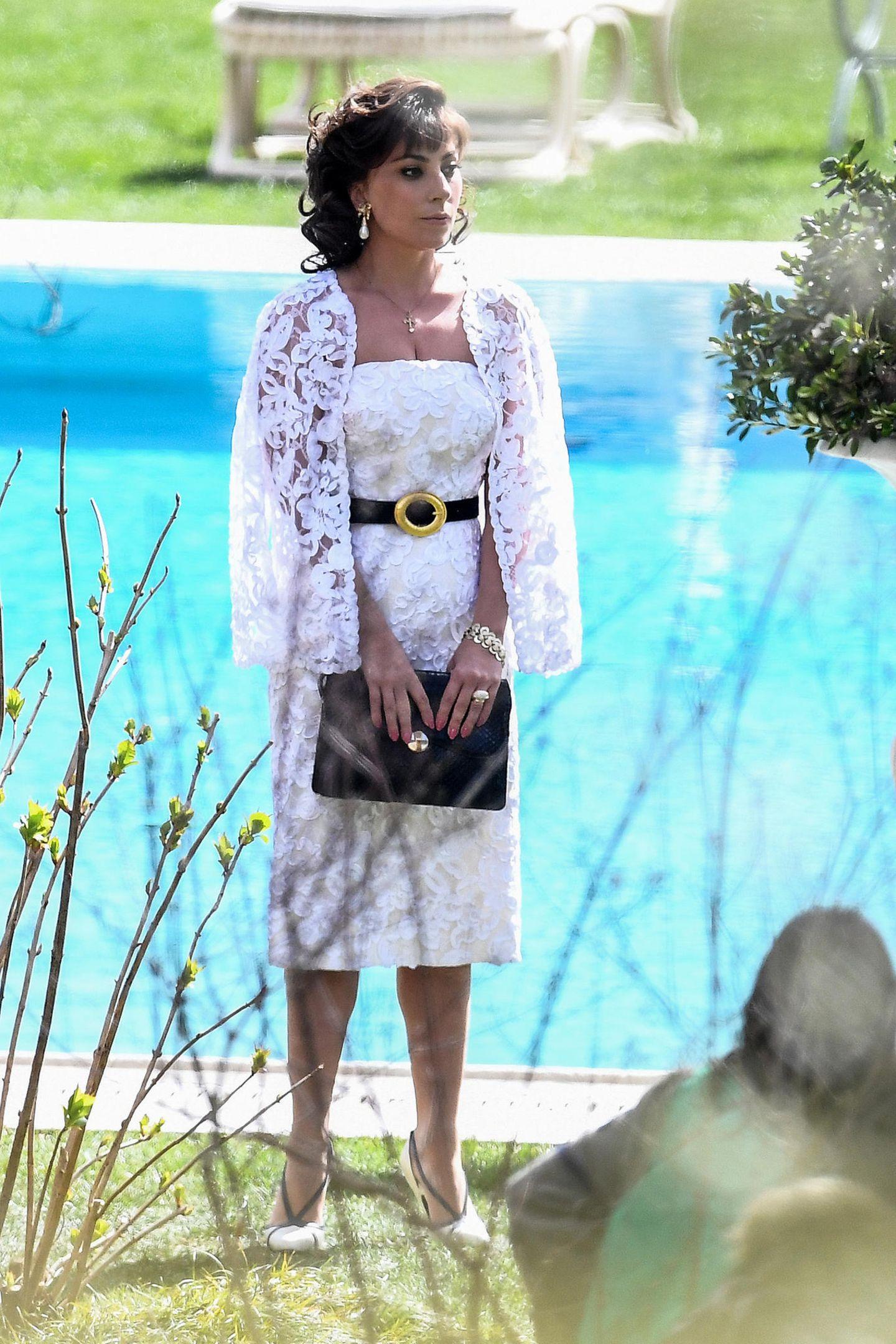 """Eigentlich kennt man diesen Megastar in wilden Outfits und Plateauheels. Umso ungewohnter, dass man Lady Gaga am Set ihres neuen Films """"House of Gucci"""" nun im weißen Spitzenkleid mit passender Jacke sieht. Fast hätte man die 34-Jährige nicht erkannt."""