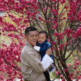 König Jigme drückt seinen kleinen Sohn liebevoll an sich. Für diesen besonderen Fototermin wählt das Königshaus von Bhutan den Garten des Lingkana-Palasts aus.