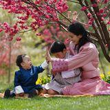 High five, Geburtstagskind! Königin Jetsun feiert mit der Familie den ersten Geburtstag ihres Sohnes Prinz Ugyen. Auch der große BruderPrinz Jigme ist bei dem kleinen Gartenfest dabei und nimmt neben seiner Mama auf der Decke Platz.