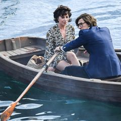"""Adam Driver legtsich mächtig ins Zeug am Set von """"House of Gucci"""". Während Lady Gaga recht entspannt die Pole-Position in dem recht wacklig wirkenden Holzbötchen einnimmt, muss ihr Kollege die Ruder schwingen. Keine einfache Aufgabe, wenn man als Darsteller des Modemoguls Maurizio Gucci in einer schmal geschneiderten Kreation des italienischen Traditionshauses steckt."""
