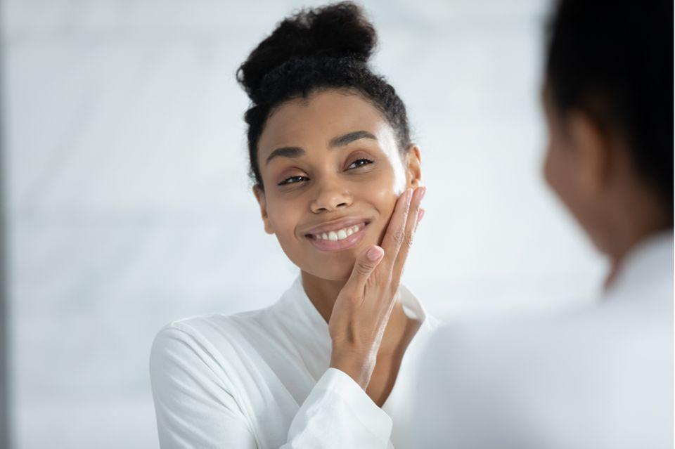 Schöne Frau benutzt Hautserum im Gesicht