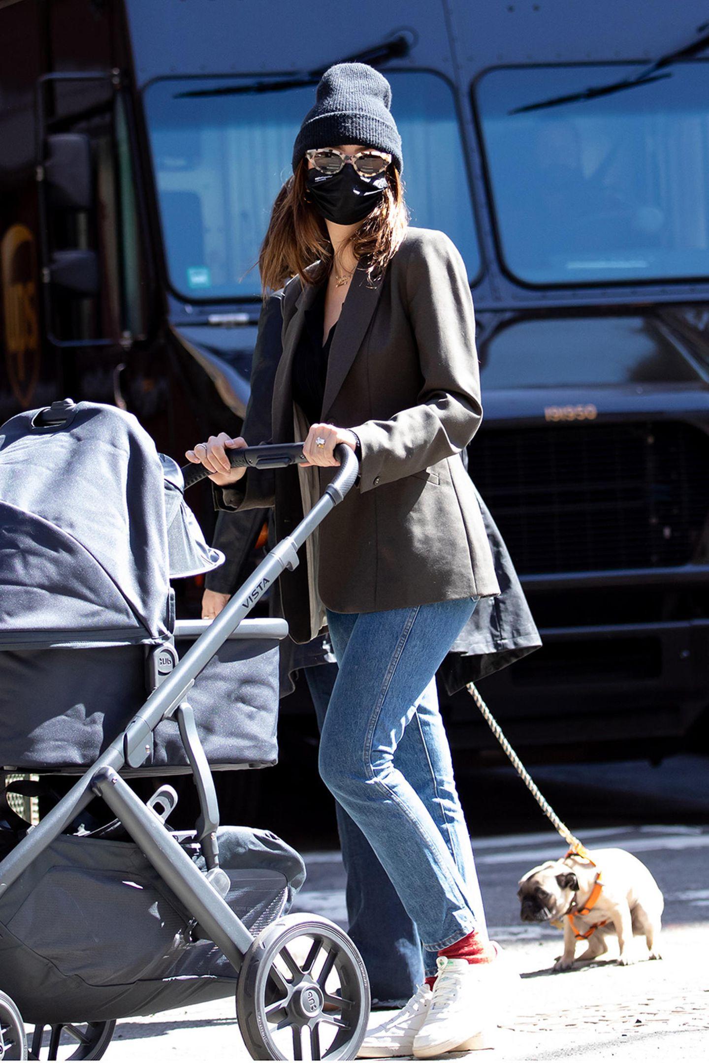 Mit Jeans und grauem Blazer ist Neu-Mama Emily Ratajkowski, hier unterwegs mit ihrem Sylvester, eher unauffällig in New York unterwegs. Aber ein knalliges Detail musste sein: die roten Socken!