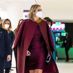 """Bei der Eröffnung der 10. Nationalen """"Week van het Geld"""" legt Königin Máxima mal wieder einen top gestylten Auftritt hin. Ihr bordeauxfarbenes Etuikleid mit passendem Mantel kombiniert Máxima mit einem knalligen Set aus Ohrringen und Kette und sorgt damit für einen tollen Farbkontrast."""