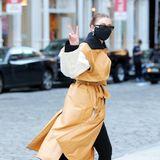 Peace! Mit stylischer Langweste in beige-gelbem Leder-Imitat ist Gigi Hadid ganz lässig in New York spazieren.