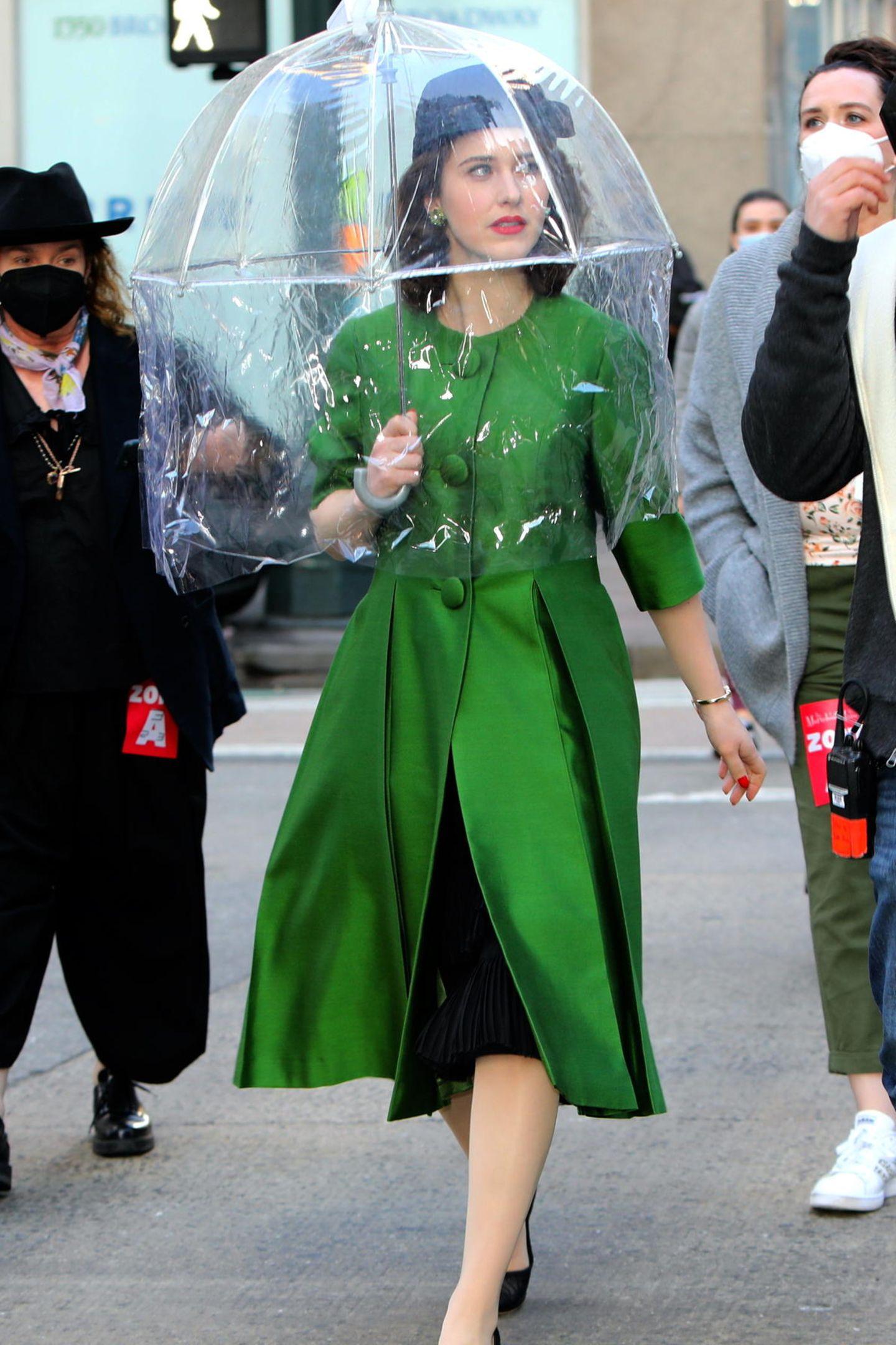 """Seit 2017 begeistert uns Rachel Brosnahan als """"Marvelous Mrs. Maisel"""" mit ihren tollen Looks, schlagfertigen Sprüchen und ihrer positiven Art. Endlich haben die Dreharbeiten zur vierten Staffel begonnen und die ersten Bilder machenjetzt schon Lust auf die neuen Folgen. Der erste Look in Smaragdgrün zeigt gleich zwei Style-Klassiker der Serie: Mantel mit ausgestelltem Schoß undHut."""