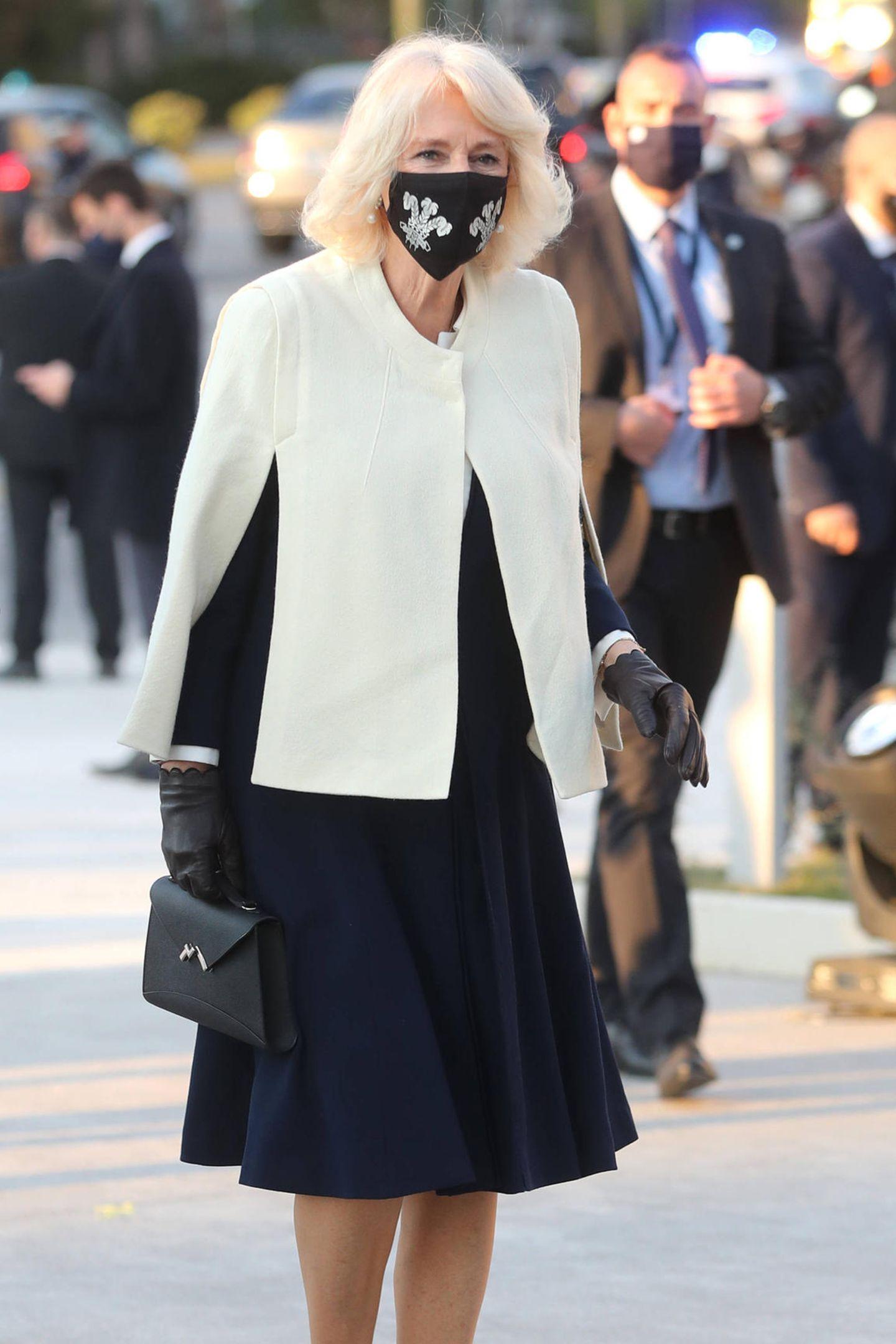 Herzogin Camilla und Prinz Charles sind nach Athen gereist um 200 Jahre Unabhängigkeit Griechenlands zu feiern. Bei der Ankunft trägt Camilla ein dunklesblaues Ensemble mit weißem Cape.