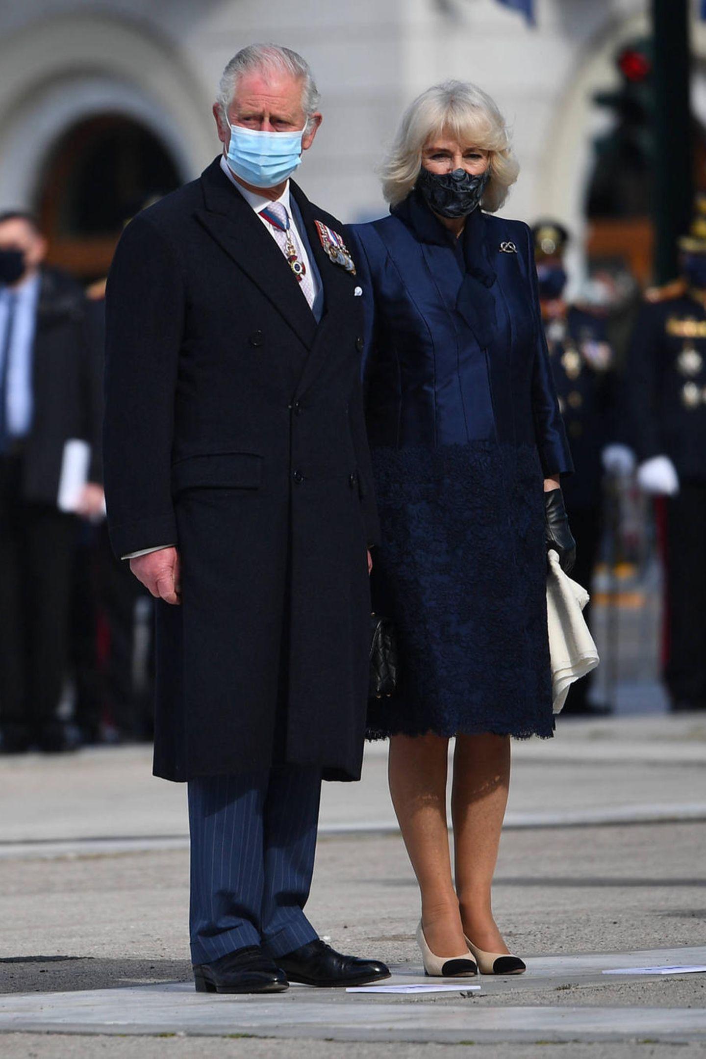 Bei einer Kranzniederlegung am zweiten Tag der Reise nach Griechenland setzt Camilla weiterhin auf Dunkelblau, diesmal aber mit Spitzensaum am Rock und aufnudefarbenePumps mit schwarzer Kappe.