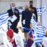 """25. März 2021  Wehende Fahnen erwarten Prinz Charles und Herzogin Camilla bei ihrem Besuch in Athen. Ein warmer Empfang zu den Feierlichkeiten der 200-jährigen Unabhängigkeit Griechenlands. Balsam für ihregestressten Seelen. Nach einem Jahr Coronapandemie, einem nervenaufreibenden Megxit und einem """"tabulosen"""" Interview von Prinz Harry und Herzogin Meghan mit der US-Talkmasterin Oprah Winfrey dürften für das britische ThronfolgerpaarSzenen wie diese neue Kraftquellen für die kommenden Herausforderungensein."""