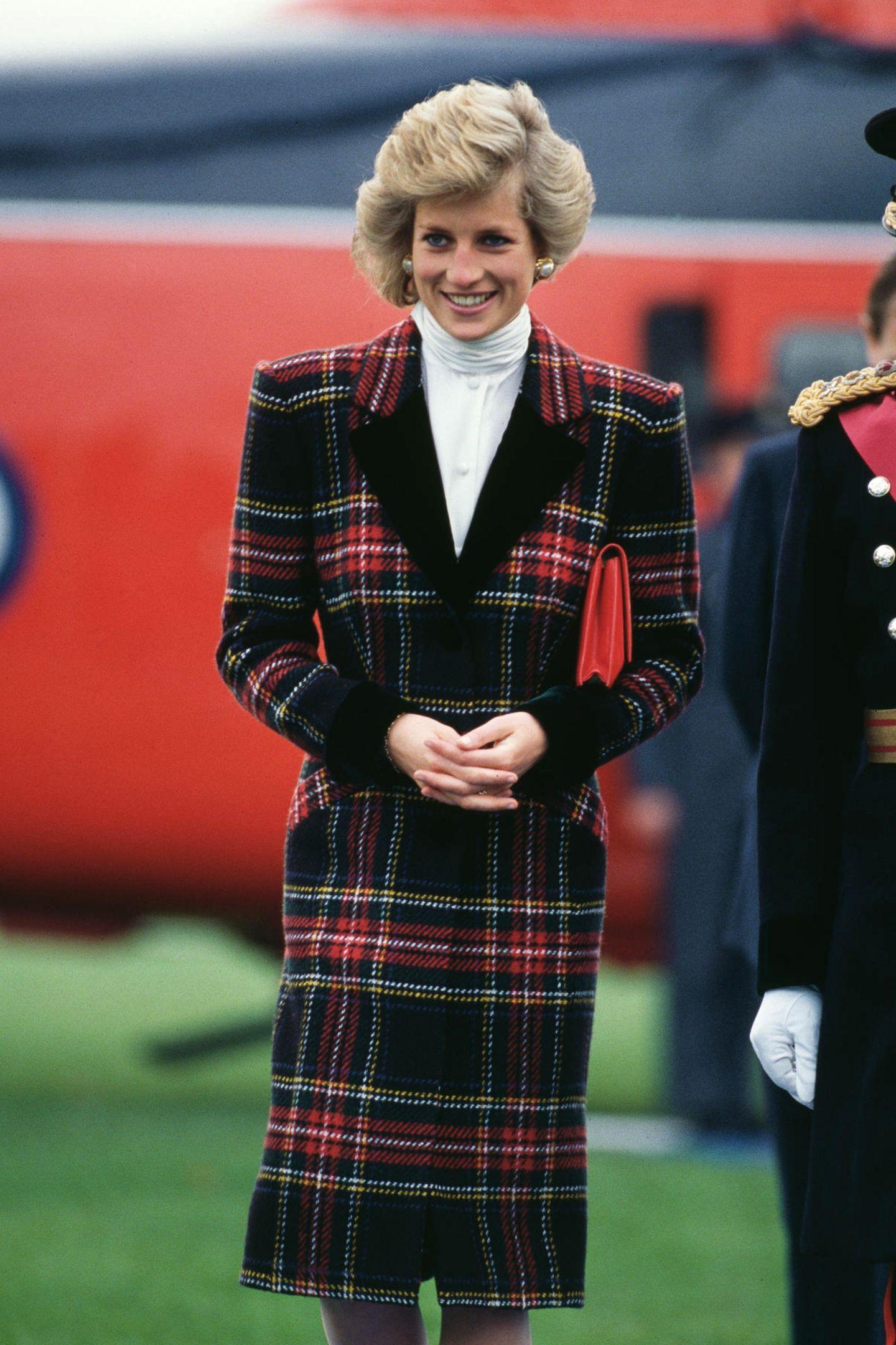 Die Vorlage des Filmlooks: Prinzessin Dianas karierter Wollmantel von Catherine Walkermit breitem Revers, Schulterpolstern und einem weißen Rollkragenpullover. Das Foto stammt aus dem Jahr 1989.