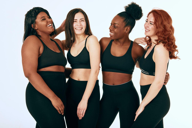 4 junge Frauen in schwarzem Sport BH und schwarzen Leggings