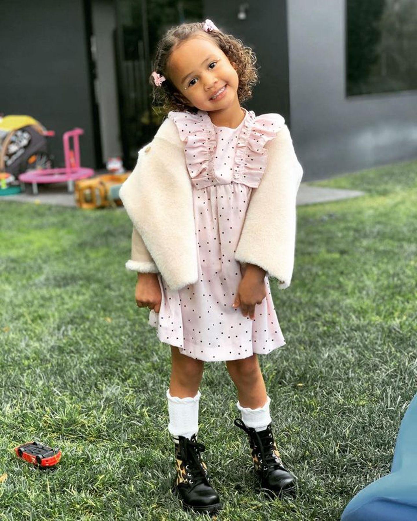 In einem rosafarbenen Pünktchen-Kleid mit Rüschen, einem flauschigen Cardigan und weißen Söckchen hat uns Chrissy Teigens Tochter Luna sofort um den Finger gewickelt. Die ebenfalls rosafarbenen Spangen und die Pose der vierjährigen setzen dem Ganzen in Sachen Niedlichkeit noch das Krönchen auf.