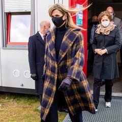 Beim Besuch eines Corona-Testzentrums in Rotterdam setzt Königin Máxima auf einen der beliebtesten Trends des vergangenen Winters: grobe Wollmäntel im Karomuster. Die Königin der Niederlande trägt ein Modell des belgischen Labels Maison Natan und kombiniert es mit spitzen Lederpumps von Gianvito Rossi.