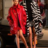 Bellas zweiter Look besteht aus Strickkleid und knallrotem Lackmantel. Neben ihr zu sehen ist Topmodel Vittoria Ceretti in einem Zebra-Mantel.