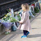 Tausende Menschen legen Blumen vor den Palasttoren in Londonnieder und kondolieren der royalen Familie – so auch dieses kleine Mädchen.