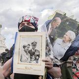 Mit Blumen und Bildern von Prinz Philip und Queen Elizabeth in der Hand zieht es diesen Londoner vor den Palast. Über den Tod des Herzogs von Edinburgh zeigt er sich sichtlich erschüttert.