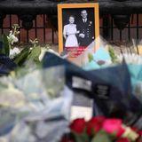 Neben den vielen Trauersträußen werden auch Fotos von Queen Elizabeth und Prinz Philip niedergelegt.