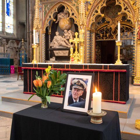 Nach dem Tod von Prinz Philip wird zu seinen Ehren ein kleiner Altar in der Westminster Abbey errichtet. Neben einem gerahmten Porträtfoto vom Herzog von Edinburgh leuchtet eine weiße Kerze. Auch ein bunter Strauß Blumen mit jeder Menge Grün ist auf dem schwarz dekorierten Tisch zu finden.