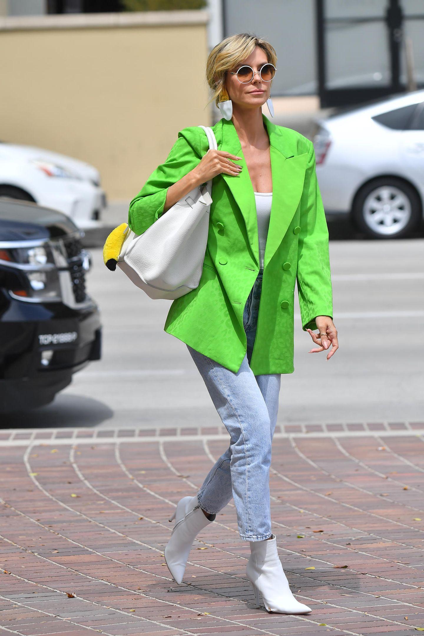 Heidi Klum total seriös? So business-like dieser Look auch wirken mag, so ist er doch vor allem ein Beweis dafür, dass in dem Topmodel eine echte Fashionista steckt. Zu verdanken hat Heidi das zum einen den weißen Boots, die mittlerweile zur Grundausstattung jedes Modeprofisgehören, und zum anderen dem Blazer in Neongrün, der im Frühling 2021 ein fulminantes Trend-Revival feiert.