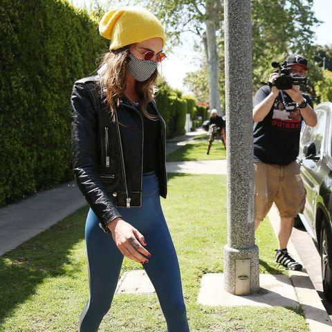 12. April 2021 Model Cara Delevingne bleibt cool, als sie inWest Hollywood auf dem Weg zum Gymvon Paparazzi umringt wird.Sie trägtLederjacke und Sonnenbrille zum engen Sport dress. DazuBeanie und Socken farblich abgestimmt in sonnengelb.