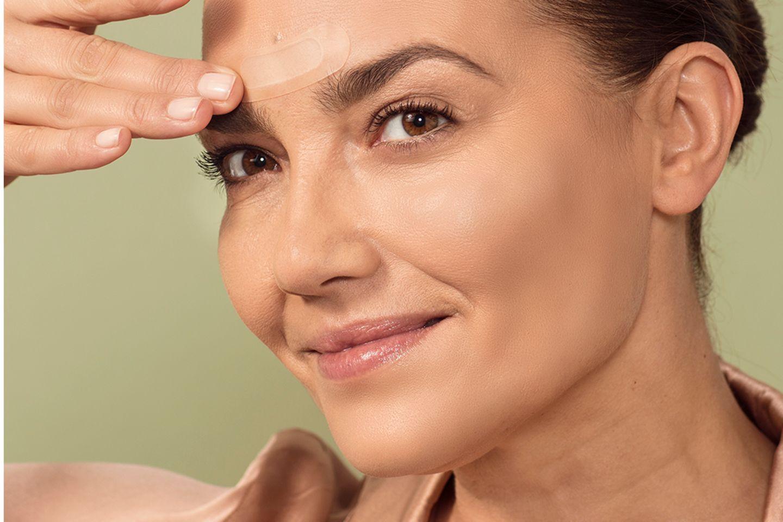 Frau benutzt And Shine Youth Patches im Gesicht