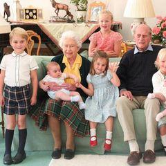 Königskinder zu Gast bei Uroma und Uropa! Wie das aussieht, zeigen die britischen Royalsmit diesem bisher ungesehenen, von Herzogin Catherine geschossenen Foto aus dem Jahr 2018, dasQueen Elizabeth und ihrenkürzlich verstorbenen Ehemann,Prinz Philip,mit sieben ihrer zehnUrenkel zeigt. Es ist das erste Mal, dass ein Foto der jüngsten Generation auf Schloss Balmoral in Schottland veröffentlicht wird. Prinz George trägt eine niedliche Shorts mit Karomuster und Kniestrümpfe. Seine Schwester Charlotte und seine Cousinen Savannah, Isla Phillips und Mia Tindalltragen Blumenkleider, weiße Strümpfe und Sandalen. Die beiden jüngsten Urenkel auf dem Bild, Prinz Louis und Lena Tindall, sind in hellen Outfits und Söckchen zu sehen.