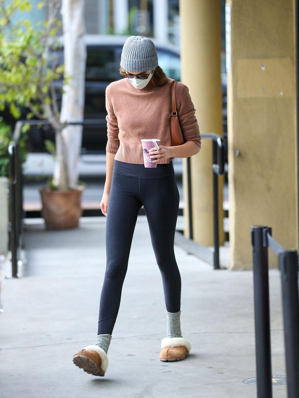 Kaia Gerber hat bereits im letzten Jahr ihre Leidenschaft für gemütliche Slippers entdeckt. Können wir gut nachvollziehen, denn ihre Lammfellschlappen von UGG sindkuschelig weich – auf der Straße, in Kombination mit grauen Wollsocken werden sie allerdings zum No-go.