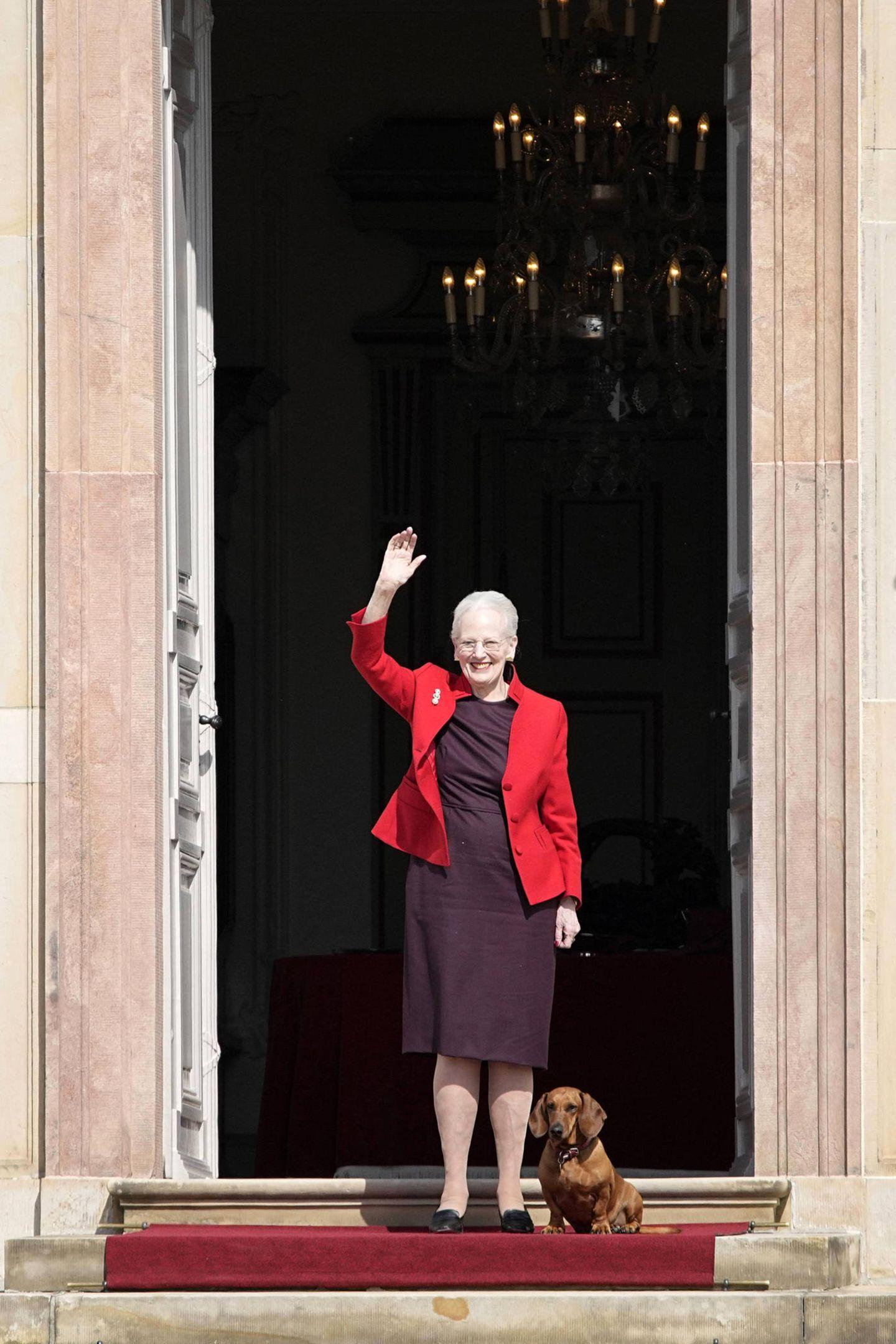 16. April 2021  Mit einem großen Lächeln im Gesicht winkt Königin Margrethe von Dänemark ihren Gratulanten vor Schloss Fredensborg zu. An diesem Tag feiert sie ihren 81. Geburtstag und lässt sich bei strahlendem Sonnenschein auf der Schlosstreppe blicken. Doch sie ist nicht allein: Begleitet wird sie von ihrem Lieblingsdackel, der brav neben der Königin wartet, während sie sich all die Glückwünsche aus der Ferne abholt.