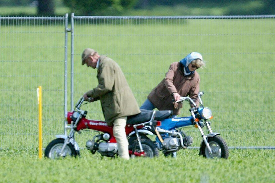 Prinz Philip (†) und Penelope Knatchbull besteigen ihre Mini-Motorräder während der Royal Windsor Horse Show im Home Park, Windsor Castle, am 13. Mai 2005.