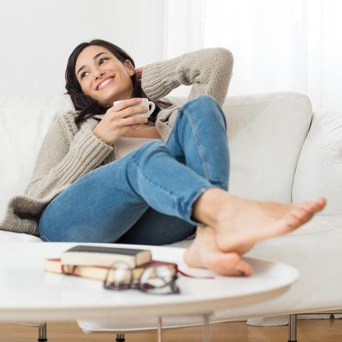 Frau liegt entspannt auf dem Sofa