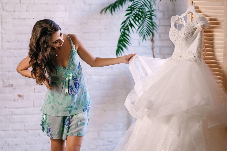 Brautkleid-Aufbewahrung: Frau betrachtet ihr Brautkleid