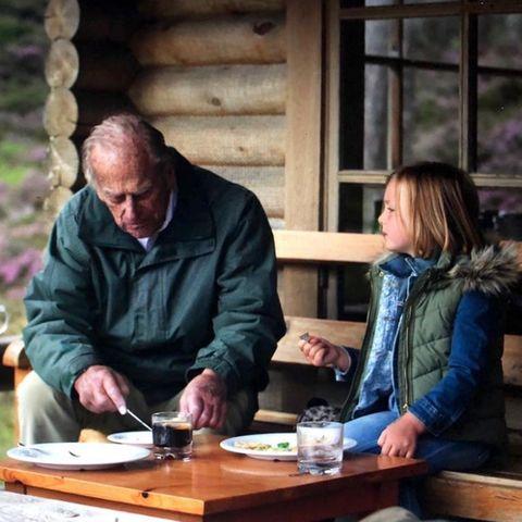 """16. April 2021  Am Vorabend der Trauer für Prinz Philip auf Schloss Windsor teilt Mike Tindall, der Ehemann von Prinz Philips Enkelin Zara, dieses schöne Foto auf Instagram. Es zeigt Philip mit Mia, der ältesten Tochter von Mike und Zara. Die beiden haben es sich vor einer Hütte gemütlich gemacht und genießen ein Brotzeit. """"Es war eine sehr traurige Woche, aber siehat uns Zeit gegeben, über großartige Erinnerungen und Geschichten nachzudenken [...]. Ein hingebungsvoller Familienvater, den wir für immer vermissen, aber immer lieben werden"""", schreibt Mike dazu. Das Foto hat, wie so oft, Herzogin Catherine gemacht."""
