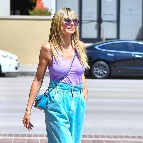 Aktuell zeigt sich Heidi Klum modisch von einer ganz neuen Seite: Sie setzt auf verschiedene Farbkombinationen in einem Look. Diesmal greift sie zu einer blauen Paperbag-Jeans, einem lilafarbenen Top und türkisfarbenen Pumps. Zu viel des Guten oder genau die richtige Mischung? Dieses Outfit ist definitiv Geschmacksache.