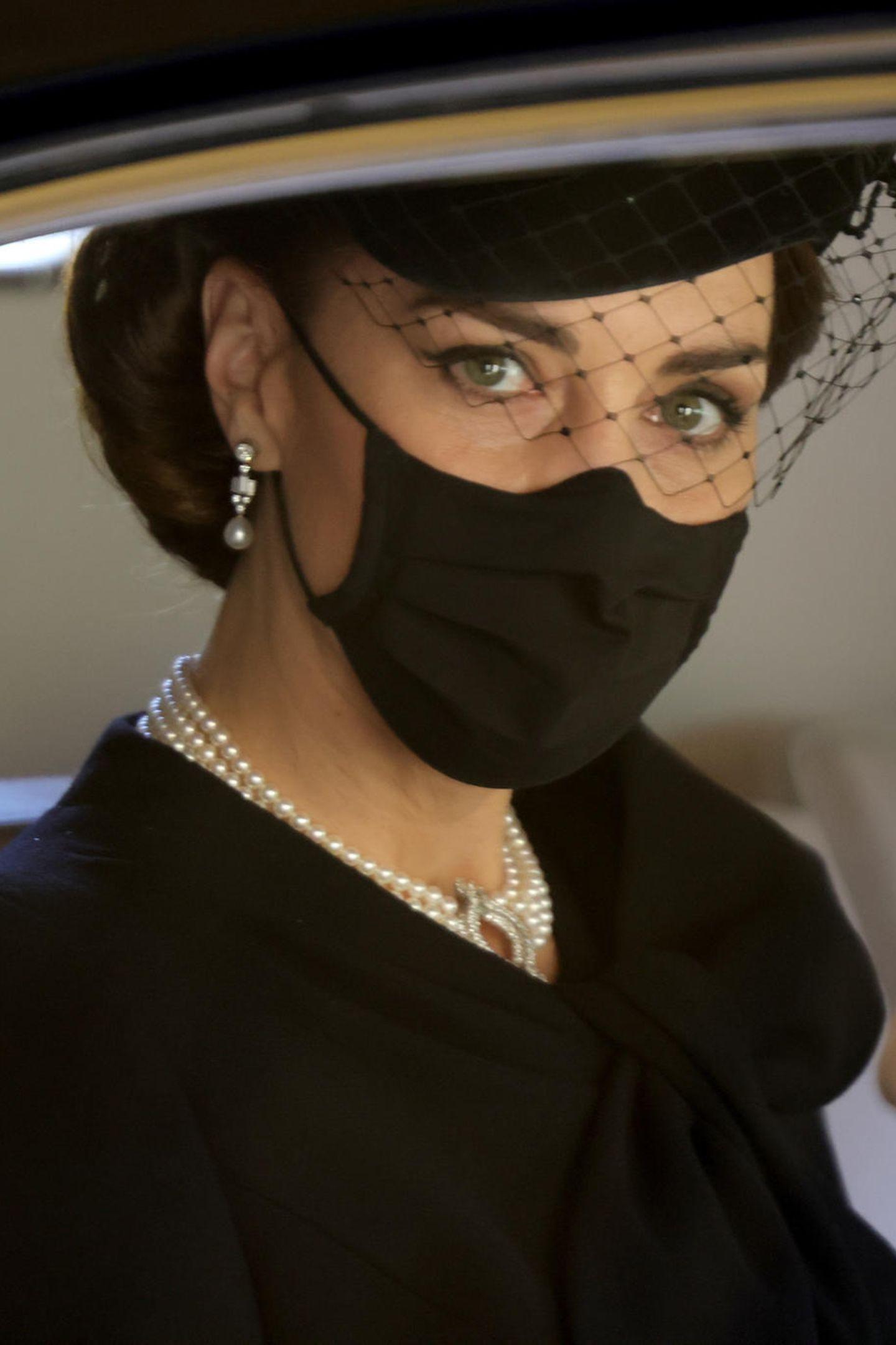 """Herzogin Catherine trägt hängende Ohrringe mit Baguette-Steinen und Perlen. Die sogenannten """"Bahrain Pearl Drop""""-Ohrringe waren ein Geschenk an Queen Elizabeth zur Hochzeit mit Prinz Philip im Jahr 1947. Kate trug sie schon in der Vergangenheit oft, auch Sophie von Wessex hat die besonderen Schmuckstücke schon getragen. Für den Tag, an dem sich die Queen von ihrem geliebten Ehemann verabschieden muss, die perfekte Wahl."""