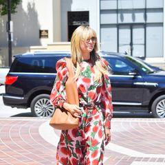 """Heidi Klums Lookmacht gute Laune: Auf dem Weg ins """"America's got talent""""-Studio trägt sie ein quietschbuntes Maxikleid. Auf den ersten Blick denkt man sofort an Erdbeeren – aber beigenaueremHinsehen wird klar, dass der pinkfarbene Stoff mit roten Blüten übersät ist."""