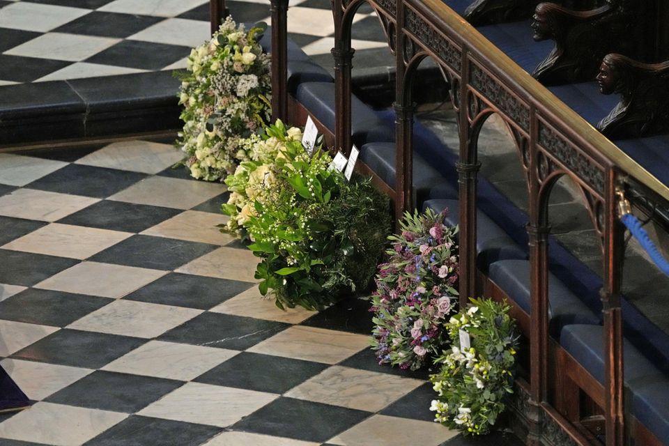 Gedenkkränze für Prinz Philip liegen in der St. George's Kappelle. Der zweite von vorne, mit violetten und fliederfarbenenBlumen, ist von Herzogin Meghan und Prinz Harry.