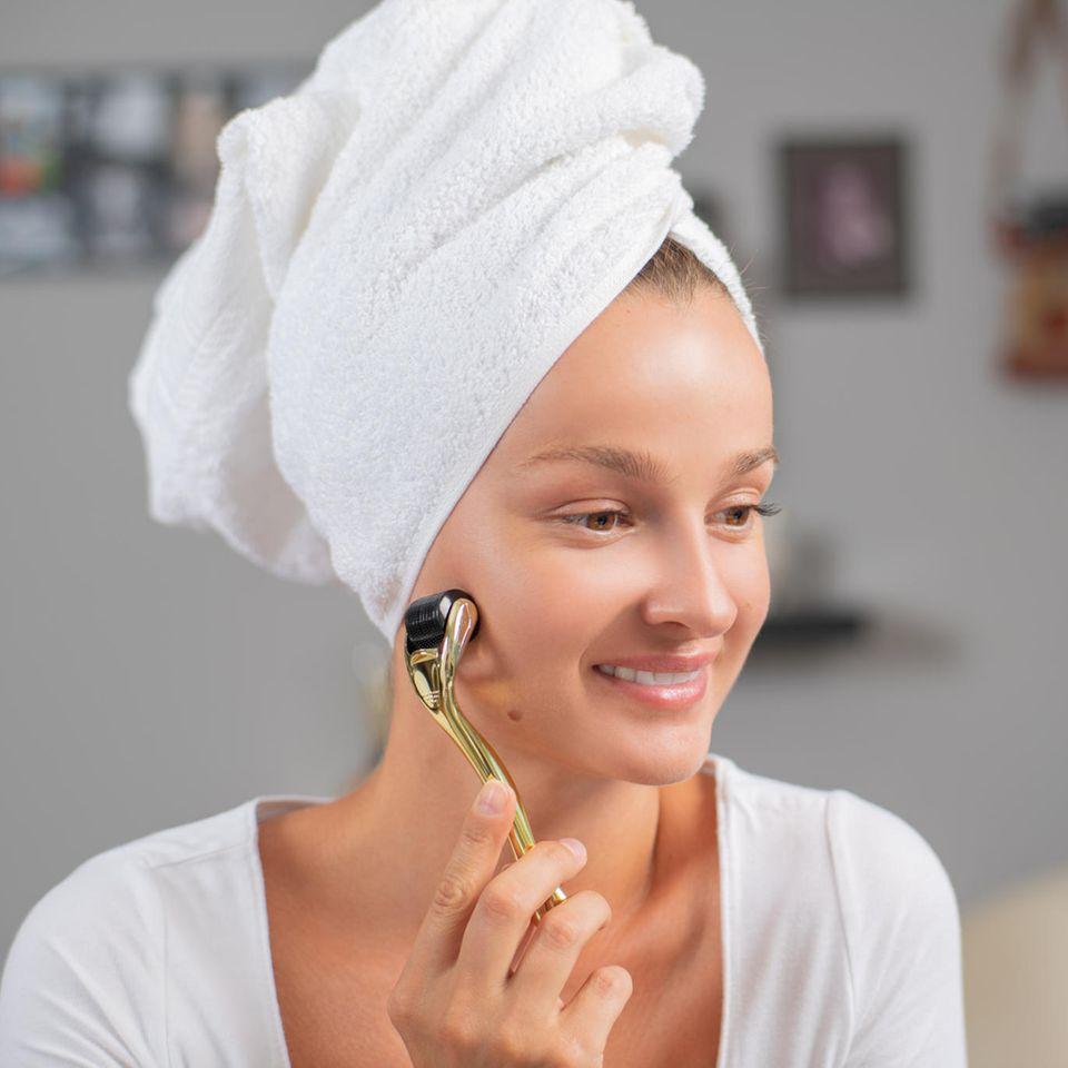 Junge Frau mit Dermaroller, schöne Haut