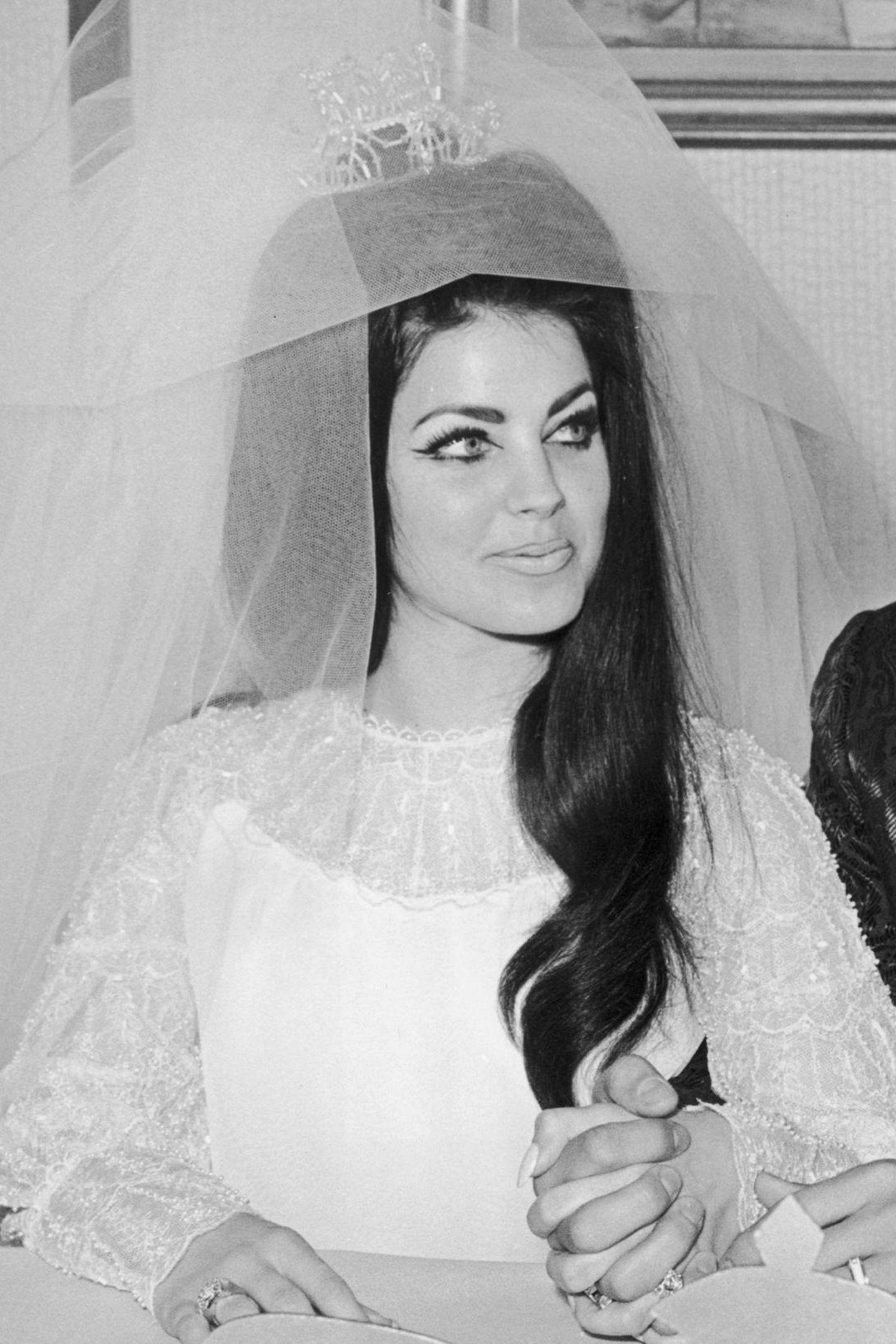 Was für eine Braut:Priscilla Presley beeindruckt 1967 auf ihrer Hochzeit mit einem besonderen und schon fast kunstvollen Augen-Make-up. Sie trägtextravaganteCat Eyes mit Winged Eyelinerund Fake Lashes. IhremarkantenAugenbrauen umrahmen ihr Gesicht optisch.