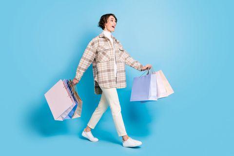 Glückliche Frau mit Einkaufstüten nach Shopping mit Gutschein