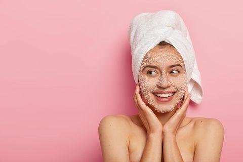 Lächelnde Frau mit pflegender Kosmetik von flaconi