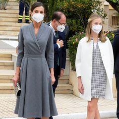 Königin Letizia wählt ein graues Blazerkleid in Midilänge. Kronprinzessin Leonor trägt kurzes kariertes Kleid, darüber einen Eggshape-Mantel von Adolfo Dominguez. Der Hingucker: Ihre spitzen roten Ballerinas.