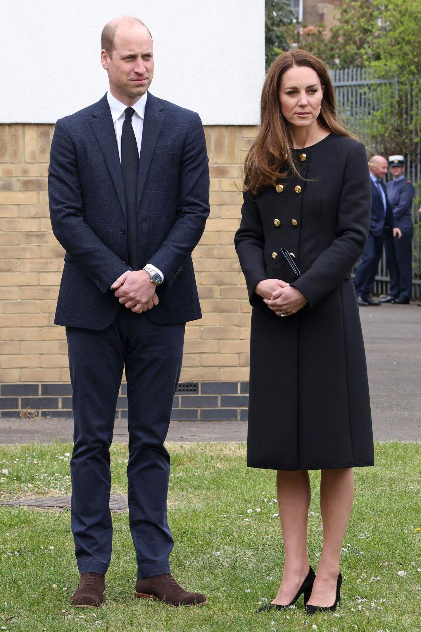 """Prinz William und Herzogin Kate besuchen die """"Air Cadets"""" in London. Zu diesem Anlass sowie als Zeichen ihrer anhaltenden Trauer um den kürzlich verstorbenen Prinz Philip tragen die Royals dunkle Farben. Und auch in Sachen Schmuck hält es die Herzogin an diesem Tag schlicht, wenngleich ihre Ohrringe eine rührende Hommage an ihre Schwieger-Großmutter, die Queen, sind, die an diesem Tag ihren95. Geburtstag feiert."""