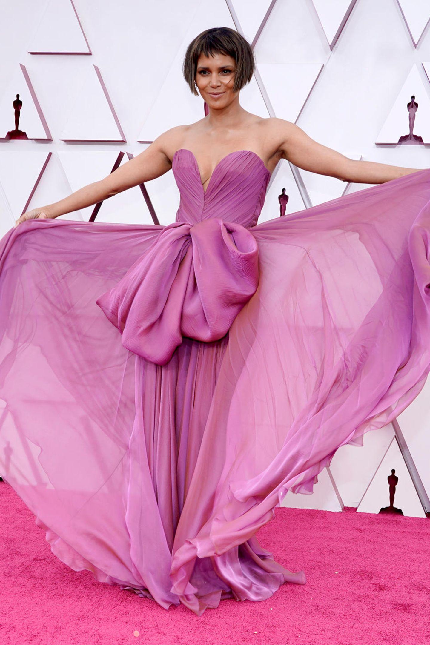 Wow, was für ein Auftritt von Halle Berry bei den Oscars 2021. Sie trägt eine schulterfreie Robe von Dolce & Gabbana in frühlingshaftenPinktönen.